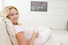 Pregnant woman watching television smiling Stock Images