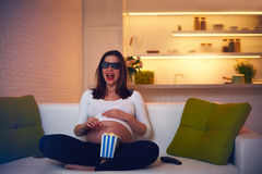 Pregnant woman watching thrilling movie at home alone Royalty Free Stock Photos