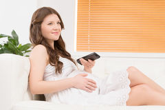 Pregnant woman watching TV. Royalty Free Stock Photography