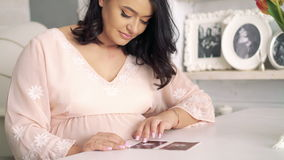 Pregnant woman watching ultrasound picture of baby at the table. 4k.  stock footage