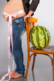 The pregnant woman and water-melon. The pregnant woman with a pot-belly costs near a chair with a water-melon in studio stock photos