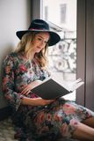 Pregnant Woman Wearing Green, Red, and White Floral Dress Reading a Book Near Window Royalty Free Stock Images