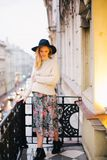 Pregnant Woman Wearing White Sweater and Multicolored Floral Skirt Standing on Balcony Stock Photography