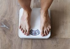 Pregnant woman weighing herself closeup royalty free stock image