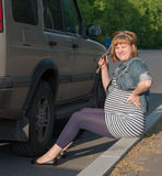 Pregnant Woman with Wheel Brace near Car Stock Photography