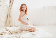 Pregnant woman in white clothes in the bedroom interior royalty free stock photos