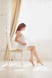 Pregnant woman in white clothes in the bedroom interior Stock Photos
