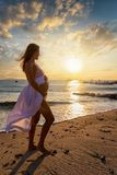 Pregnant woman stands at a beach during sunset time. Pregnant woman in white dress and exposed belly stands at a beach during sunset time royalty free stock photography
