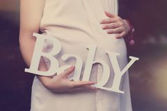 Pregnant woman in white dress holds word `Baby` made of white wooden letters outdoors stock photography