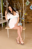 Pregnant woman in a white dress on a swing Stock Photos
