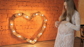 Pregnant woman in white dress on wooden background heart stock video footage