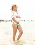 Pregnant woman in white hat posing on sandy beach Royalty Free Stock Image