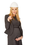 Pregnant woman in white helmet pointing on you Stock Photo