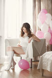 Pregnant woman in a white nightgown with balloons. Stock Photography