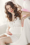 Pregnant woman in a white nightgown in the bedroom. Royalty Free Stock Image