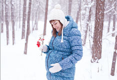 Pregnant woman in winter forest Stock Photo