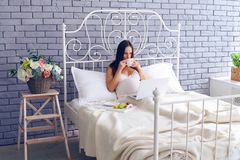 Pregnant woman working in bed and having breakfast. Wide shot of pregnant woman working in bed and having breakfast Royalty Free Stock Image