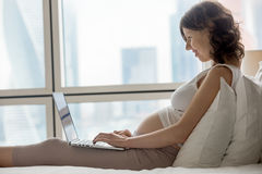 Pregnant woman working at home Royalty Free Stock Images