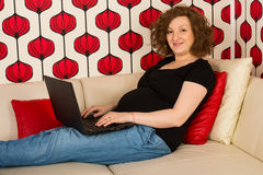 Pregnant woman working on laptop home Royalty Free Stock Photos