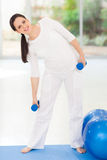 Pregnant woman working out Royalty Free Stock Images