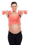 Pregnant woman working out with dumbbells Stock Photo