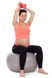 Pregnant woman working out with dumbbells Royalty Free Stock Photos