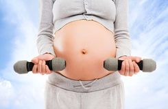 A pregnant woman working out with dumbbells Royalty Free Stock Image