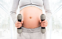 A pregnant woman working out with dumbbells Royalty Free Stock Photo