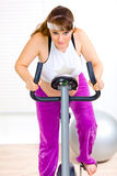 Pregnant woman working out on static bike Royalty Free Stock Photo