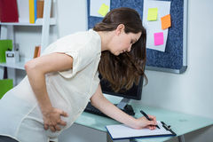 Pregnant woman writing on clipboard Stock Images