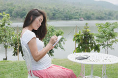Pregnant woman writing down some notes in her notebook while sit. Asian pregnant woman writing down some notes in her notebook while sittng and resting in garden Stock Photography