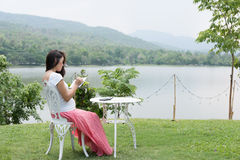 Pregnant woman writing down some notes in her notebook while sit. Asian pregnant woman writing down some notes in her notebook while sittng and resting in garden Royalty Free Stock Images