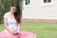 Pregnant woman writing down some notes in her notebook while sit. Asian pregnant woman writing down some notes in her notebook while sittng and resting in garden royalty free stock image