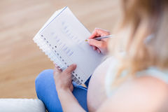 Pregnant woman writing down some notes Stock Image