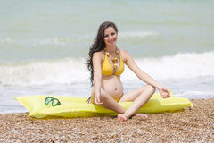 Pregnant woman in yellow bikini on pebble beach Royalty Free Stock Photo