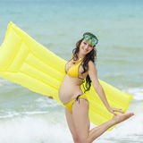 Pregnant woman in yellow bikini playing on the beach Stock Images