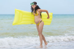 Pregnant woman in yellow bikini playing on the beach Stock Photos