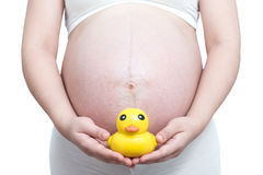 Pregnant woman with yellow duck toy on her belly Stock Photography