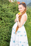 Pregnant woman with yellow flower rose on nature Stock Photos