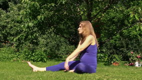 Pregnant woman yoga exercise during pregnancy outdoor at park stock footage