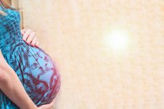 Pregnant womans belly on a light background. Sun glare effect. Copy space royalty free stock photos