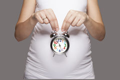 Pregnant women with alarm clock. Pregnant women with the cute tummy holding alarm clock stock photography