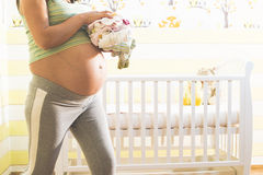 Pregnant women in a baby room. Stock Photos