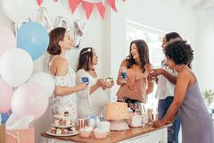 Pregnant woman celebrating baby shower party with friends Stock Photos