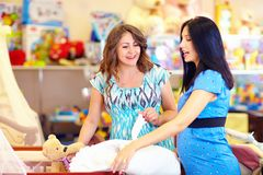 Pregnant women choosing goods for baby Royalty Free Stock Images