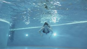 Pregnant women dives in the pool under water. stock video footage