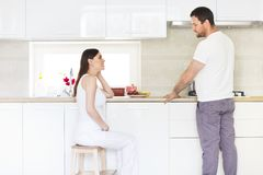 Pregnant woman and happy man in the kitchen Stock Images