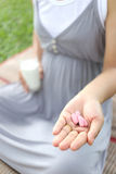Pregnant women have a glass of Milk and vitamin pill in hand to Royalty Free Stock Photos