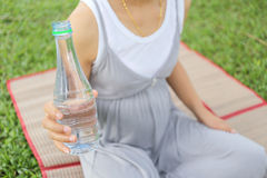 Pregnant women have a water bottle in hand. Pregnant women have a water bottle in hand to drink more water to the health of the baby Stock Photos