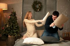 Pregnant woman with her husband before Christmas tree. stock images